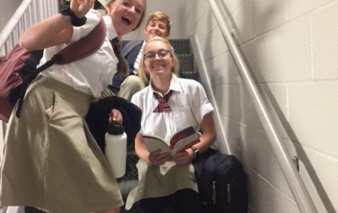 sophomore Abbie Cobb and freshman Nathan Poulsen gather around sophomore Holly Valentine as she studies in the stairwell.